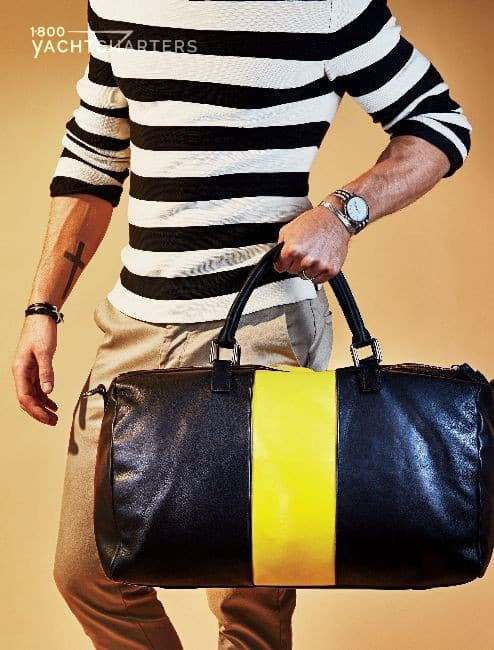 Person in horizontal blue and white striped shirt. He is holding a duffle bag. The bag is navy blue with a yellow vertical stripe.