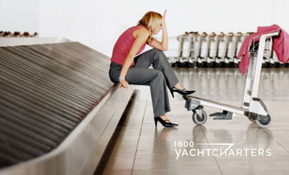 Woman sitting on an empty baggage carrousel holding head - lost luggage