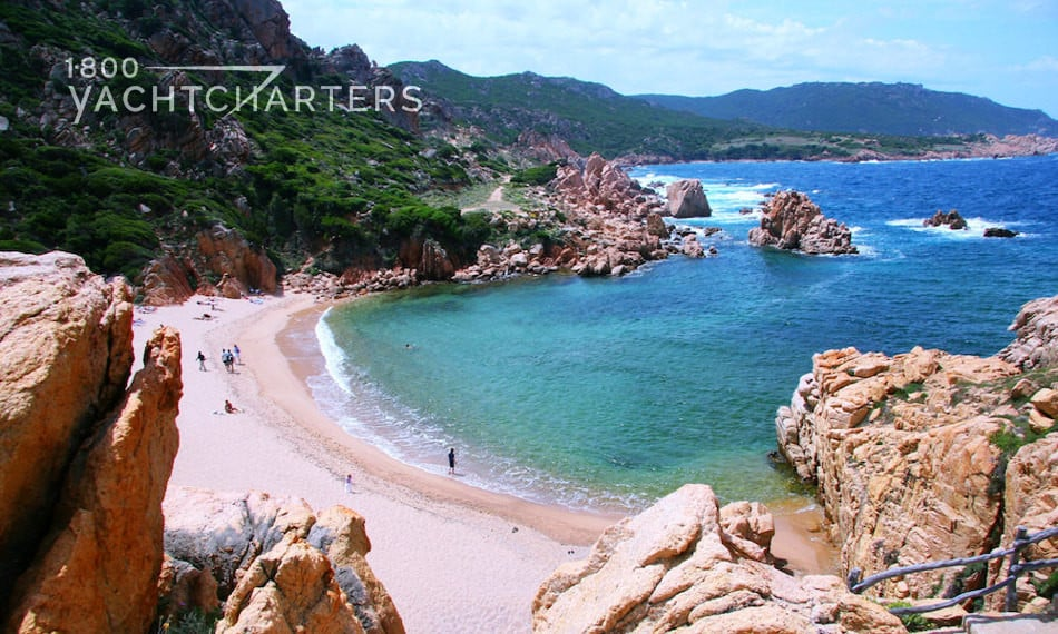Photograph of a secluded cove in Sardinia.  View from the top of a rocky cliff, looking down into a cove with turquoise water and beach.