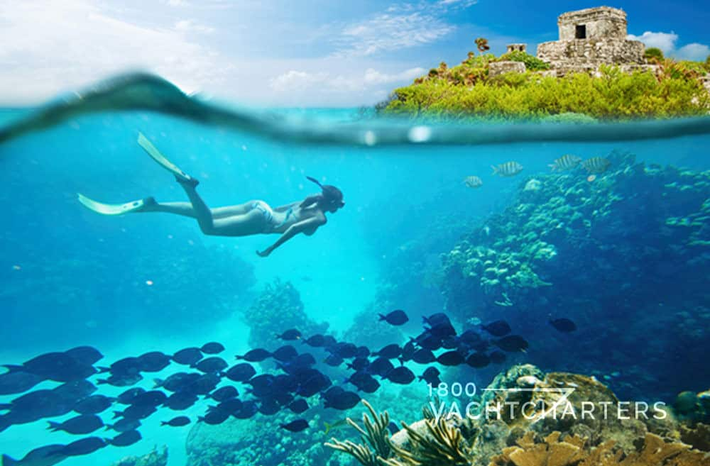 girl swimming over a reef and camera showing fish underneath her and rock formation and sky above