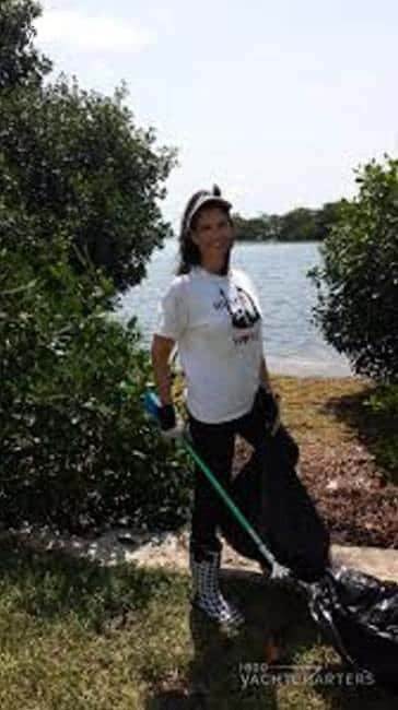 Photograph of Jana Sheeder standing next to the ocean during a beach cleanup. She is holding a grabber in one hand and a trash bag in the other. She is wearing a visor, gloves, and high boots.