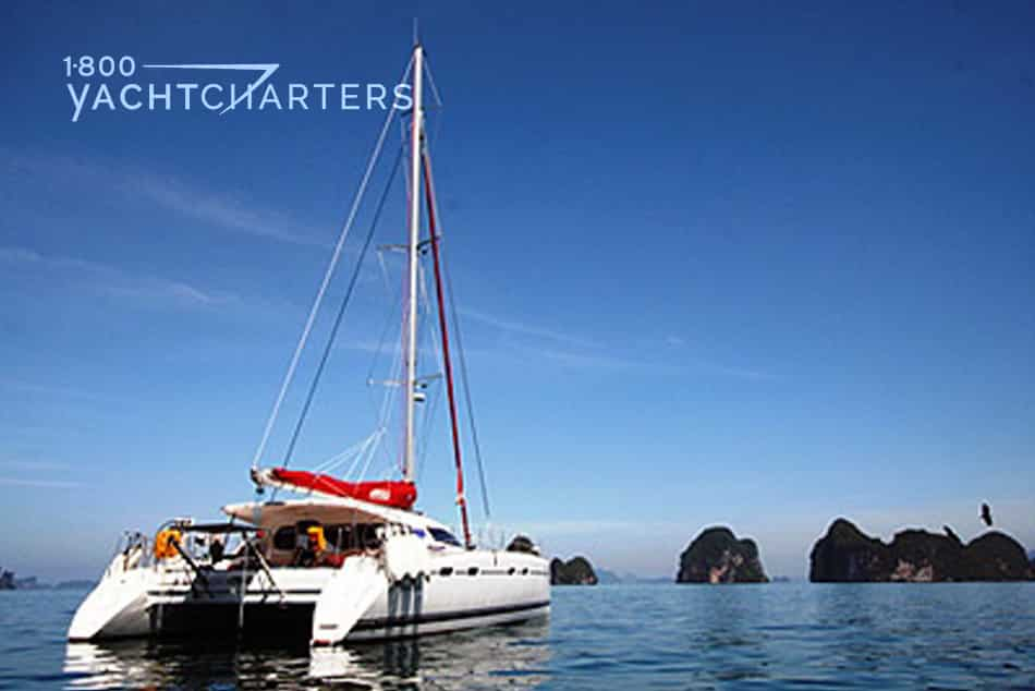 Amaia catamaran sailboat. Photo taken in a quiet bay. She is at anchor with no sails.  There are 3 large boulder islands in the distance in front of her. She has a red sail cover over the boom, and it reads the boat name, Amaia in white letters.