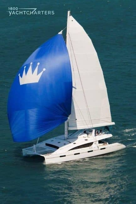 Kings Ransom catamaran sailboat photograph under sail. The front sail is royal blue with a white crown on it. The boat is sailing toward the lower left side of the picture