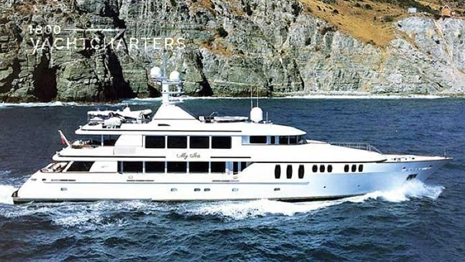 my iris. photograph of superyacht iris. she is underway. headed to the right side of the photograph. there are rock cliffs behind her. the water is dark blue and is lapping at her hull.