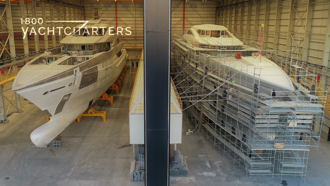 Side-by-side photographs of 2 yachts under construction in a factory.