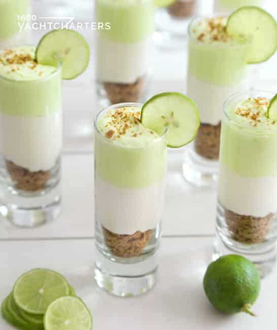 Photograph of a table covered in miniature key lime pies in parfait cups with cucumber slices on the edges. The table is covered with a white tablecloth.  There are green key limes between the parfait cups.