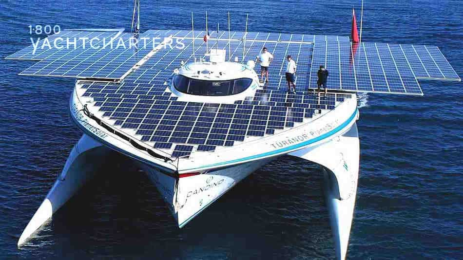Planetsolar catamaran yacht photo. Aerial picture of the top of the catamaran yacht.  There are multiple people on the top of the yacht.