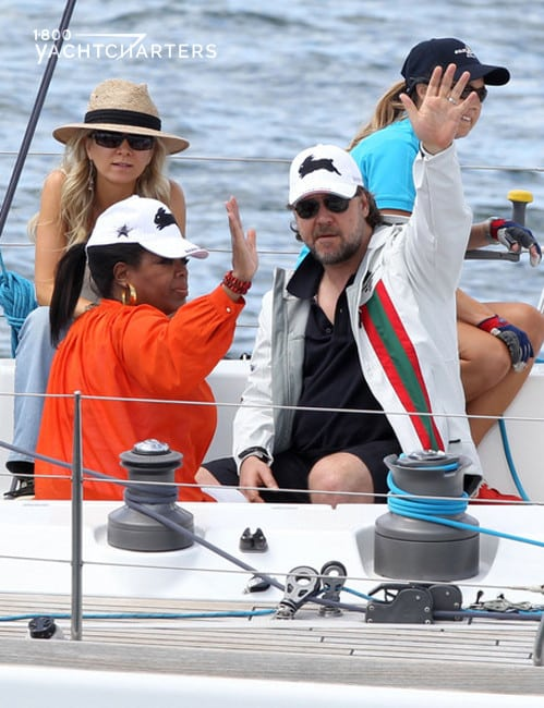 Photograph of Russell Crowe and Oprah Winfrey on the deck of a sailboat. They are waving.