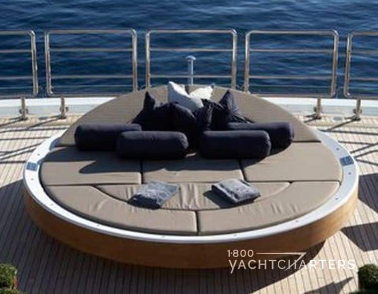 solar-powered circular suntan sunbed with head and pillows lifted up on yacht deck