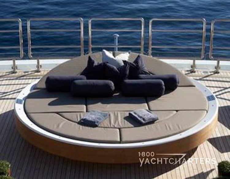 solar-powered circular suntan sunbed with head and pillows lifted up on yacht deck