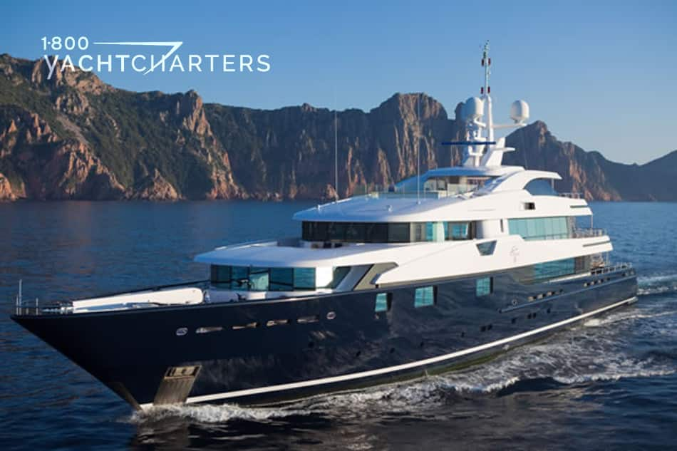 Cloud 9 motoryacht. Photo taken from the front left side of the yacht as it is running. Waves lapping at the hull. Mountain in background. Black hull. White superstructure.