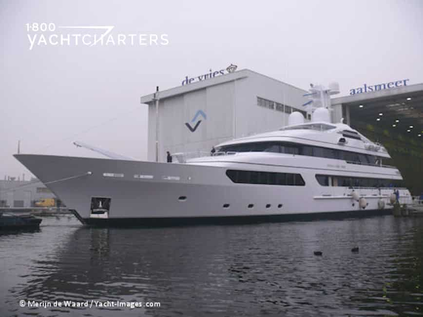 Photograph of profile of motoryacht at De Vries plant. Big white boat. Photo seems like black and white photography, but mostly because it is foggy and dark.