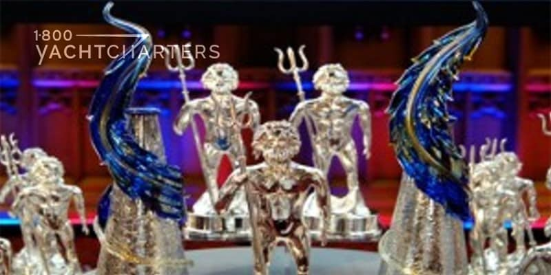 Photograph of World Superyacht Award trophies. They look like little men holding King Neptune pitchforks. Multiple figurines sitting on a tiered table. Background in red, black, and blue.