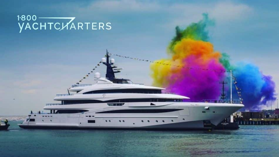 Photograph of CLOUD 9 yacht launch. She is a big white powerboat, at a dock, with streamers of flags going across her radar balls at the top of the yacht. There is a plume of colored smoke going across her bow. The colors are green, yellow, purple, and deep blue.