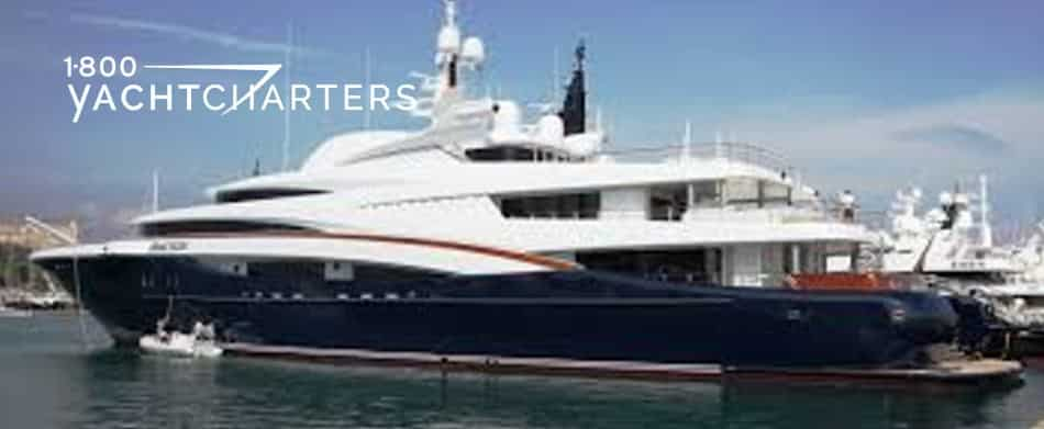 Photo of superyacht Anastasia profile from left. Dark blue hull with red pinstriping. Whie superstructure.