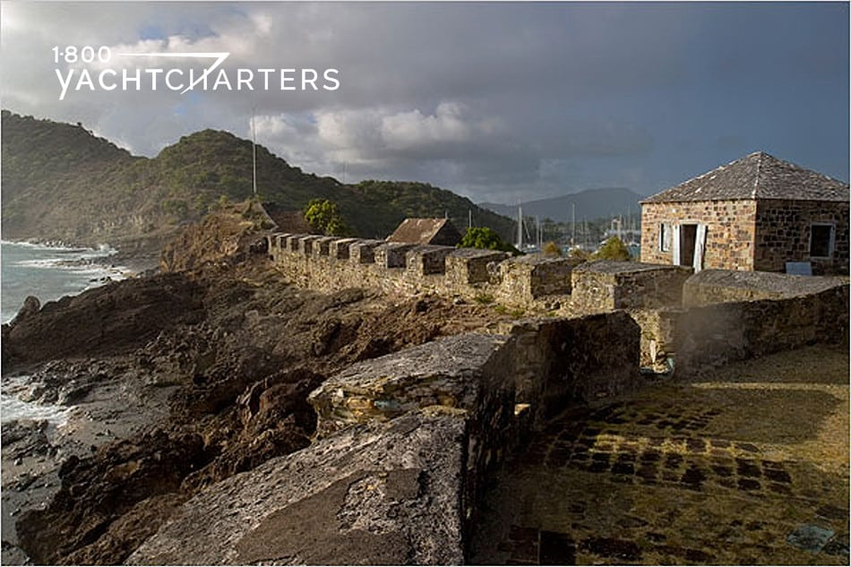 Antigua photo. Picture taken from far end of fort. Shows a mountain in the background, with a stone fort and rock walls in the foreground, spanning to the end of the photo.