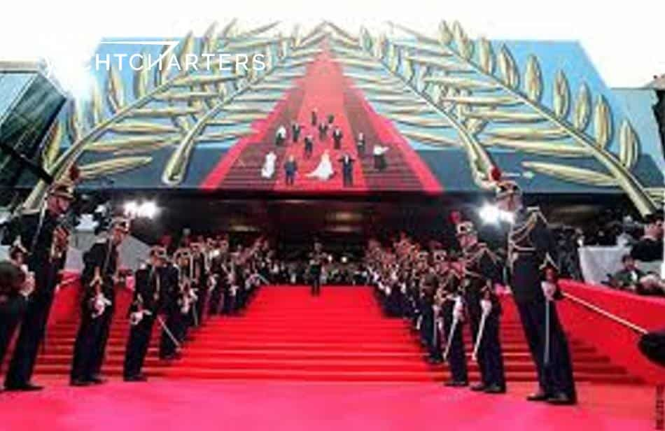 celebrity runway. Photograph of red carpet staircase at Cannes Film Festival., Stairway is bordered on boat sides by uniformed guards. Building has large red image of extended red carpet, surrounded by wreath that is hand drawn.