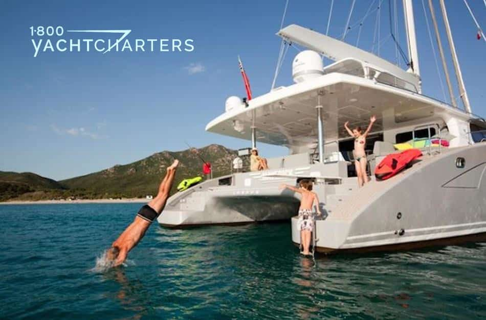 Photograph of a catamaran sailboat at anchor, while charter guests sit with feet in the water or dive off and swim from the boat.