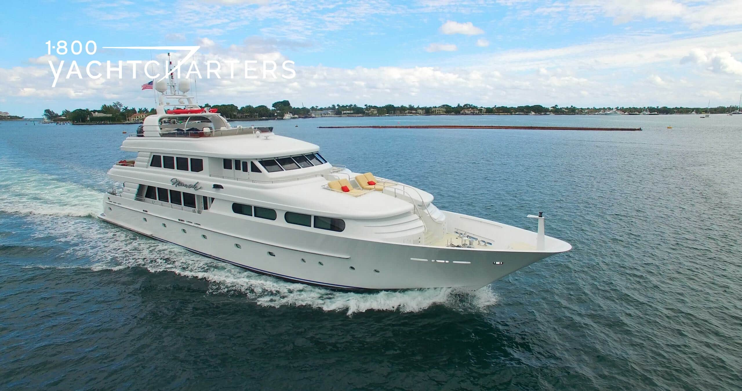 Review. Quarter profile photograph of motoryacht Namoh. She is heading toward the bottom right side of the photo. The yacht is all white. There is an island in the background. There are people lying on the deck of the yacht.