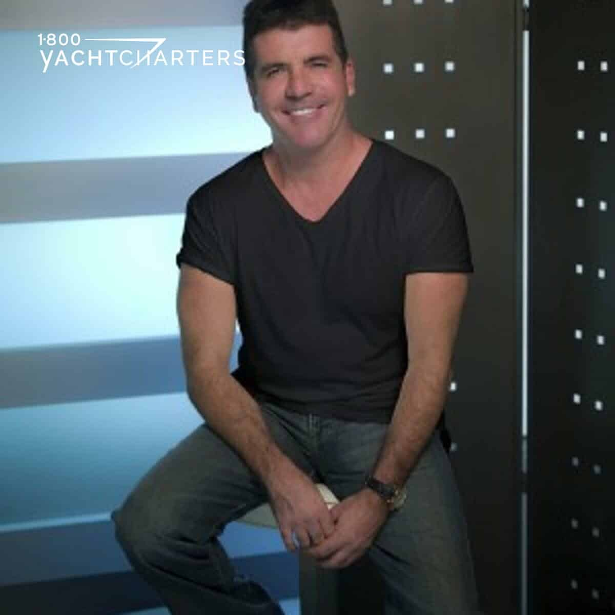 Photograph of Simon Cowell smiling in front of a grey wall with horizontal lighting.  He is wearing a black t-shirt and blue jeans.  He is sitting on a stool.
