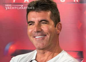 Photograph of Simon Cowell smiling in front of a bright red backdrop. He's wearing a white t-shirt.