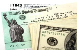 photo of hundred dollar bills and tax refund paperwork. A 1040 form is underneath them