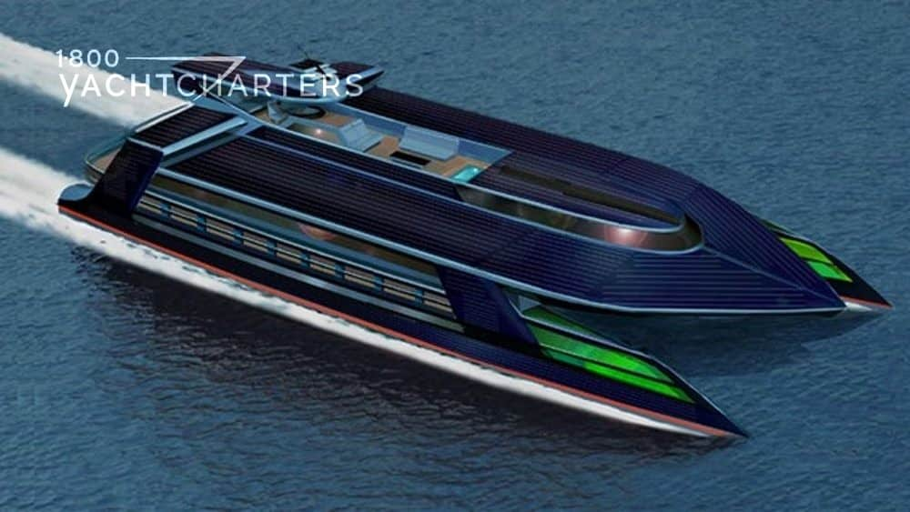 Aerial photograph of solar-powered catamaran, Ocean Empire. Yacht is dark blue with bright green horizontal stripes across the bow. She has solar panels on the flat roof