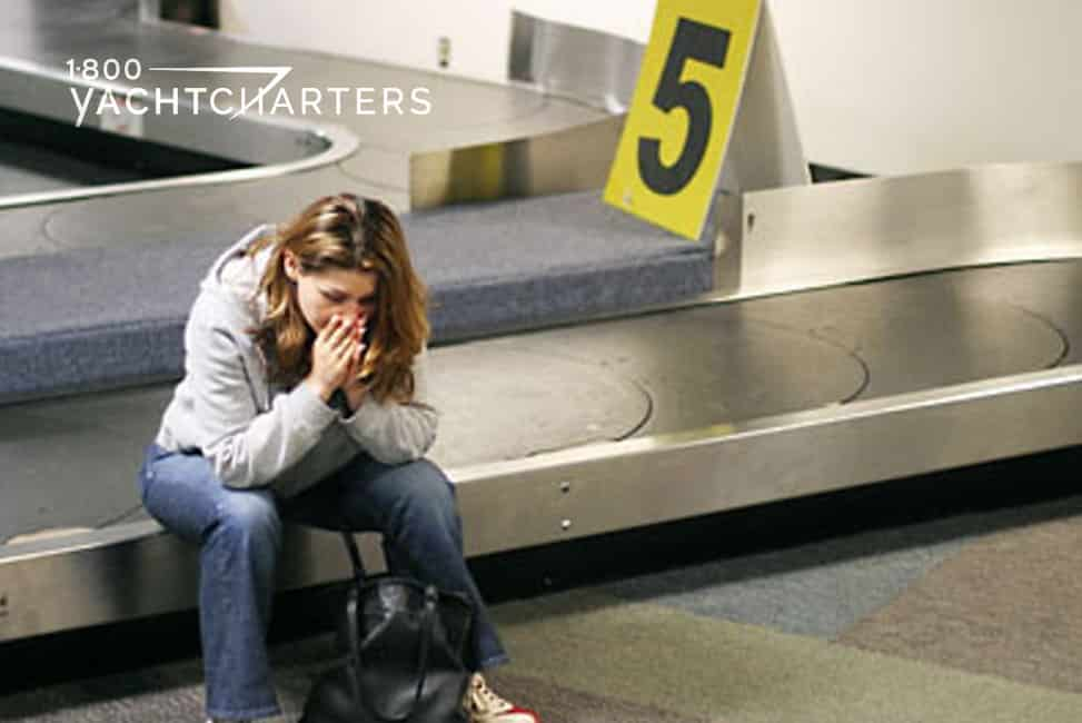 Photo of a young woman sitting on a baggage claim carousel. She has her head in her hands. There is no luggage on the carousel.