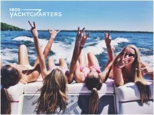 Photo of girls lying on the back of a motoryacht. They are raising peace signs in the air.