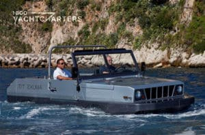 Amphibious jeep photograph. It is motoring in the water, and there is a rocky mountain behind it.  There are 2 people in the car. One man is in a white t-shirt, and the other is in a black t-shirt.