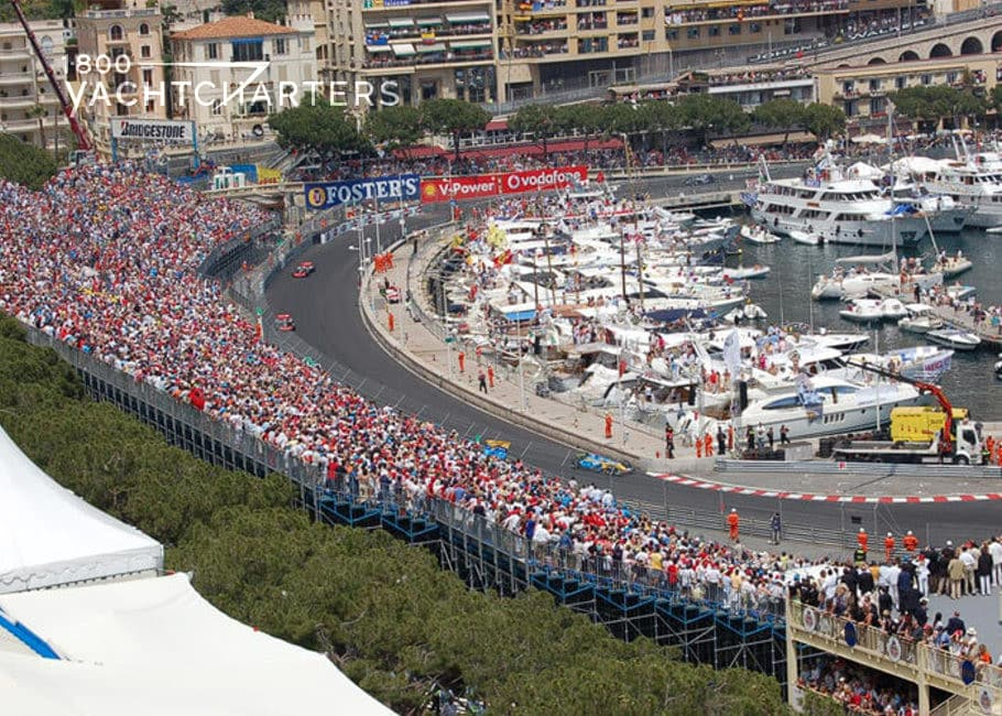 Aerial photograph of monaco grand prix race track. To the left of the photo are people in the bleachers, track in the middle (no cars on it in picture), and to the right are large yachts docked next to the race track, behind barricades