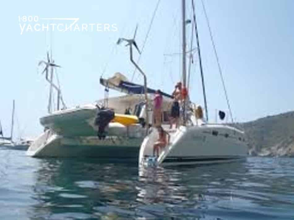 Nemo catamaran picture. Photograph of back of catamaran at anchor in Greece.  People standing on the deck, and one girl sitting close to the water, as if she's ready to go swimming.