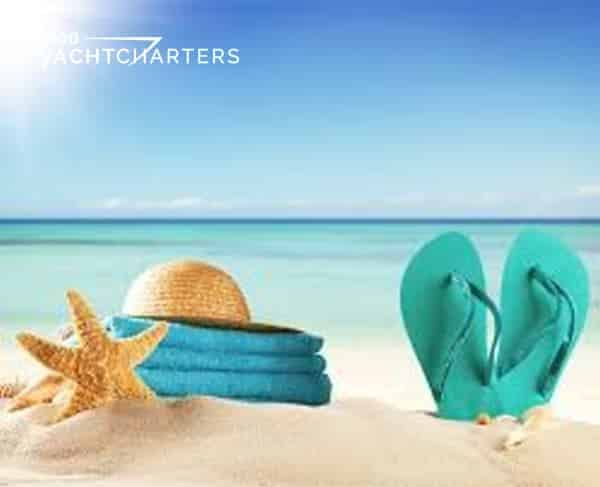 Beach with calm ocean beyond. Closeup photograph of starfish, turquoise raft, and beach hat on left side of photo.  Turquoise flip flop sandals vertically stuck in the sand on the right side of the photo.