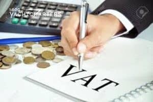 Photograph of a businessman writing on a piece of paper that says VAT. There are coins next to the piece of paper, and a computer keyboard beside it.