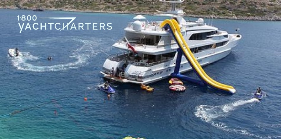 Lazy Z motoryacht photo. Picture of yacht from behind. Her inflatable slide is deployed from the top deck. It is yellow with a blue base.