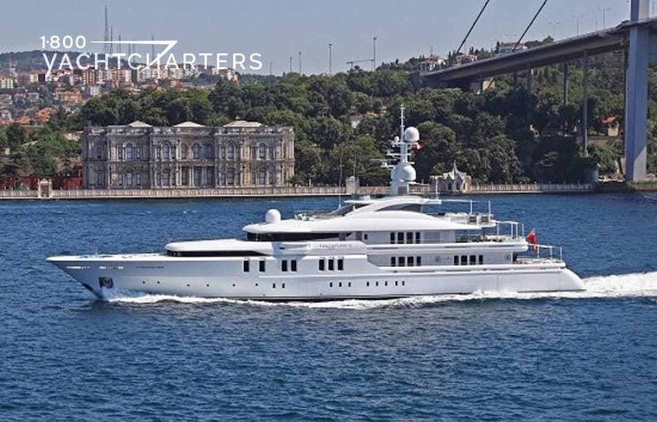 Talisman C yacht photograph.  Profile view of white superyacht cruising by a city.