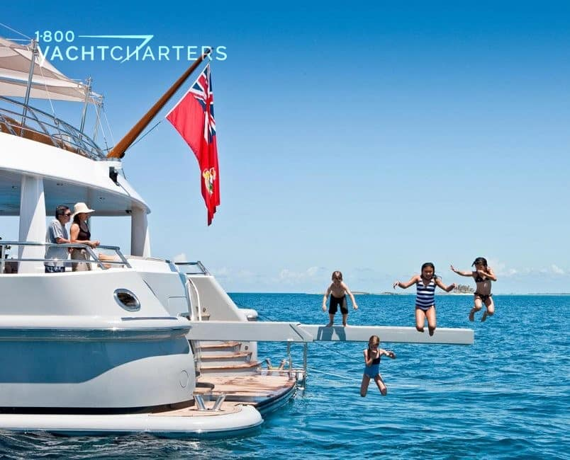 kids jumping off of diving board in photo of yacht. Back end of yacht appears in left side of photo.  Parents at the back of the yacht, looking at the kids. 4 children jumping off of yacht's diving board into the water below.  There is a bright red flag at the back of the yacht.