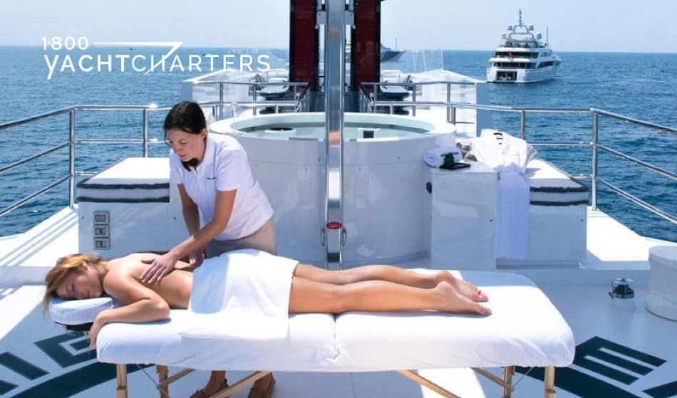 Photograph of massage therapist and client (who is on massage bed) on the back of a superyacht. There is another motoryacht anchored behind them, in the distance.