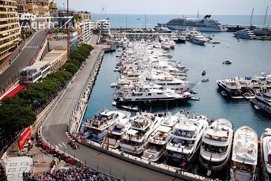 Monaco Grand Prix racetrack photo with yachts docked next to it. Yachts and water are to the center and right side of the photo. Racetrack at left and front of photo.