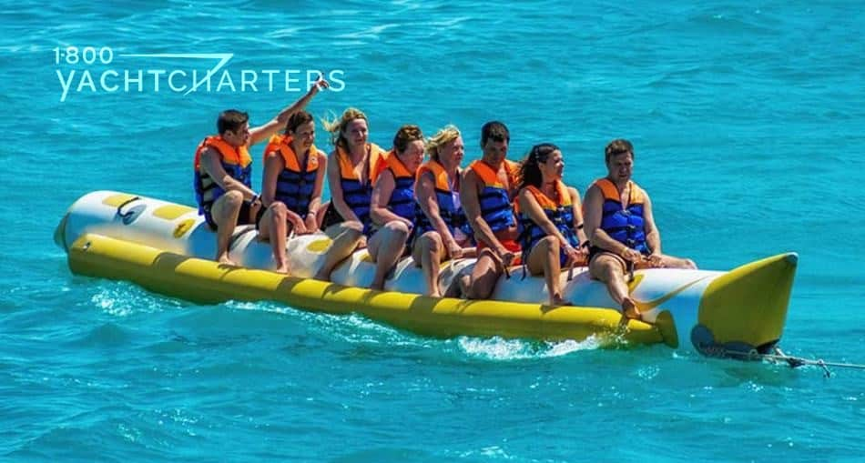 Photograph of banana boat with 9 people riding it. All are wearing orange life preservers. Banana boat is yellow.  Ocean is turquoise.