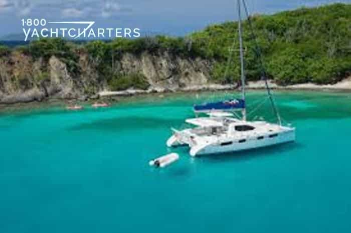 Catamaran at anchor in front of an island in the Bahamas. Gorgeous photo has turquoise water in ocean