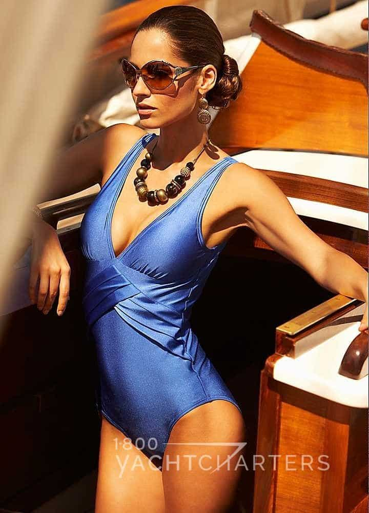 Photo of a woman leaning against a wall. She is wearing a blue one piece swimsuit and sunglasses.