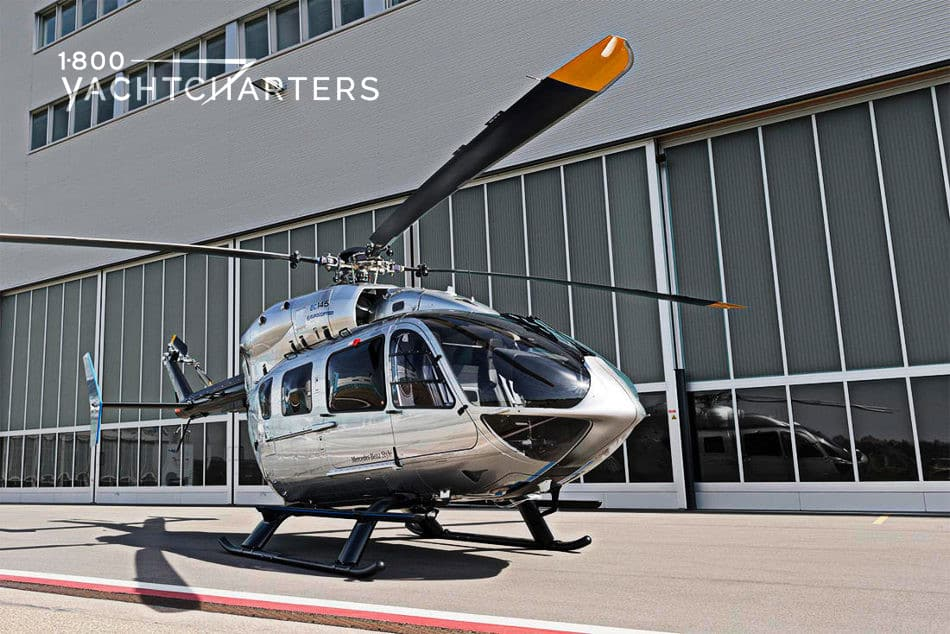 Photograph of a silver and black Mercedes Benz EC145 Eurocopter helicopter parked in front of a building with glass walls. Rotors are black with orange tips.