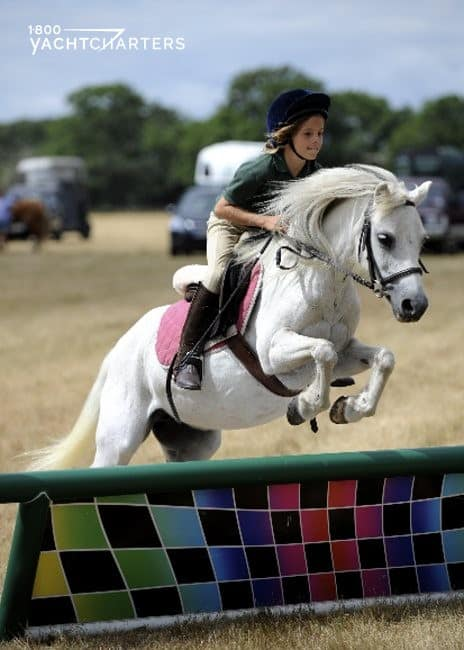 Photograph of a little girl on a white horse. The horse is jumping over a multicolored banner