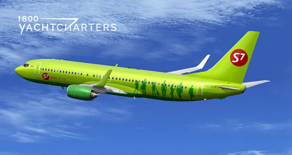 Photograph of a lime green jet flying toward the left side of the screen. The body of the jet has green people in shadow painted on it. There is blue sky below and above the plane, with clouds surrounding.