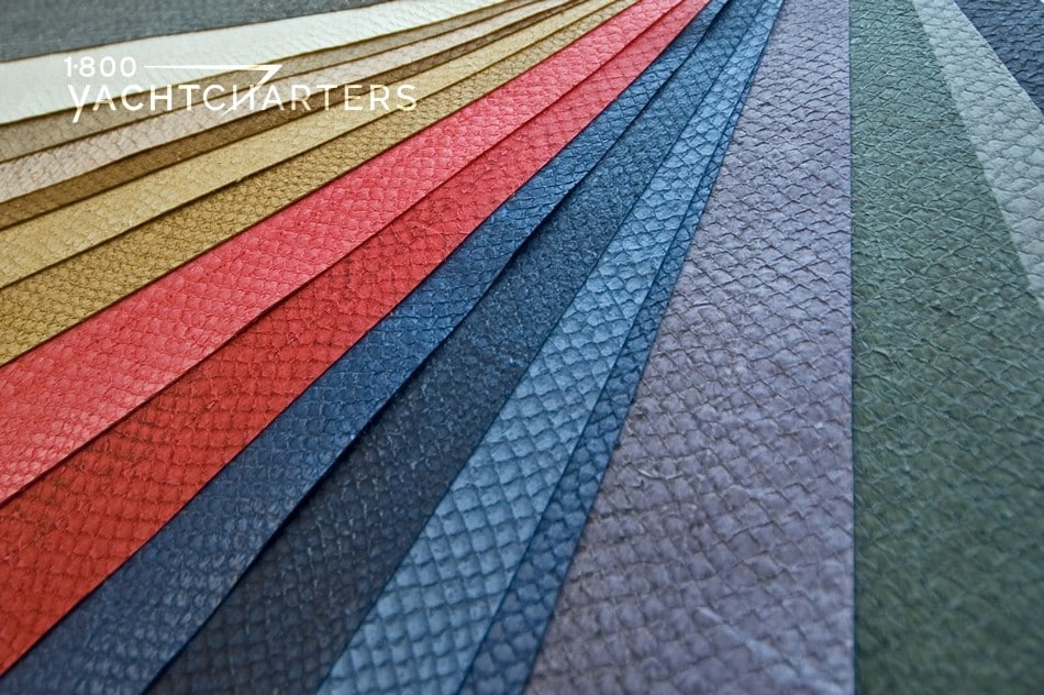 Photograph of salmon skin leather in different colors. It is used in yacht interior design and is sustainable. The colors are laid next to each other and range from dark blues to oranges and golds