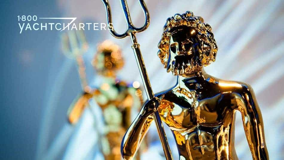 Photograph of a row of golden neptune yacht charter design awards. The statue in the background is blurred.