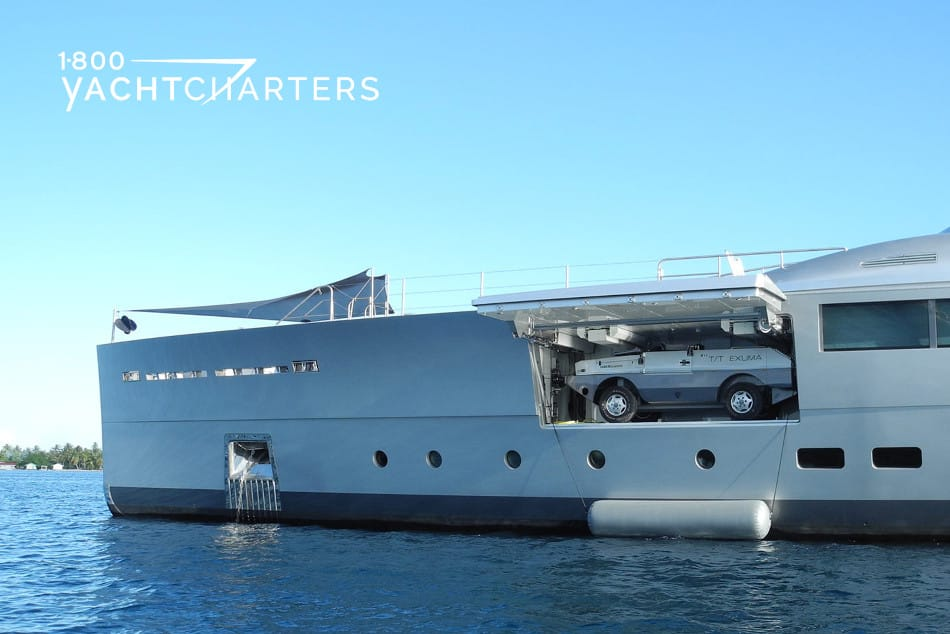 Photograph of the side of yacht Exuma.  Tender garage on the side of boat is open, and Amphibious Jeep is visible.