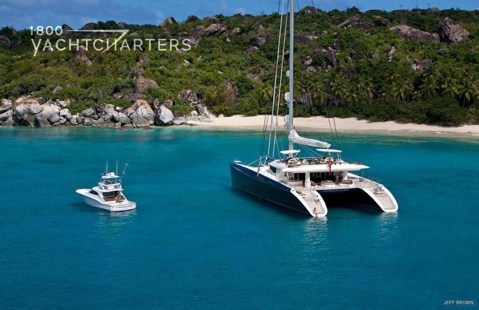 Aerial photograph of sailboat catamaran at anchor in a private cove. It is anchored next to a motoryacht. The motoryacht looks tiny next to the giant catamaran.