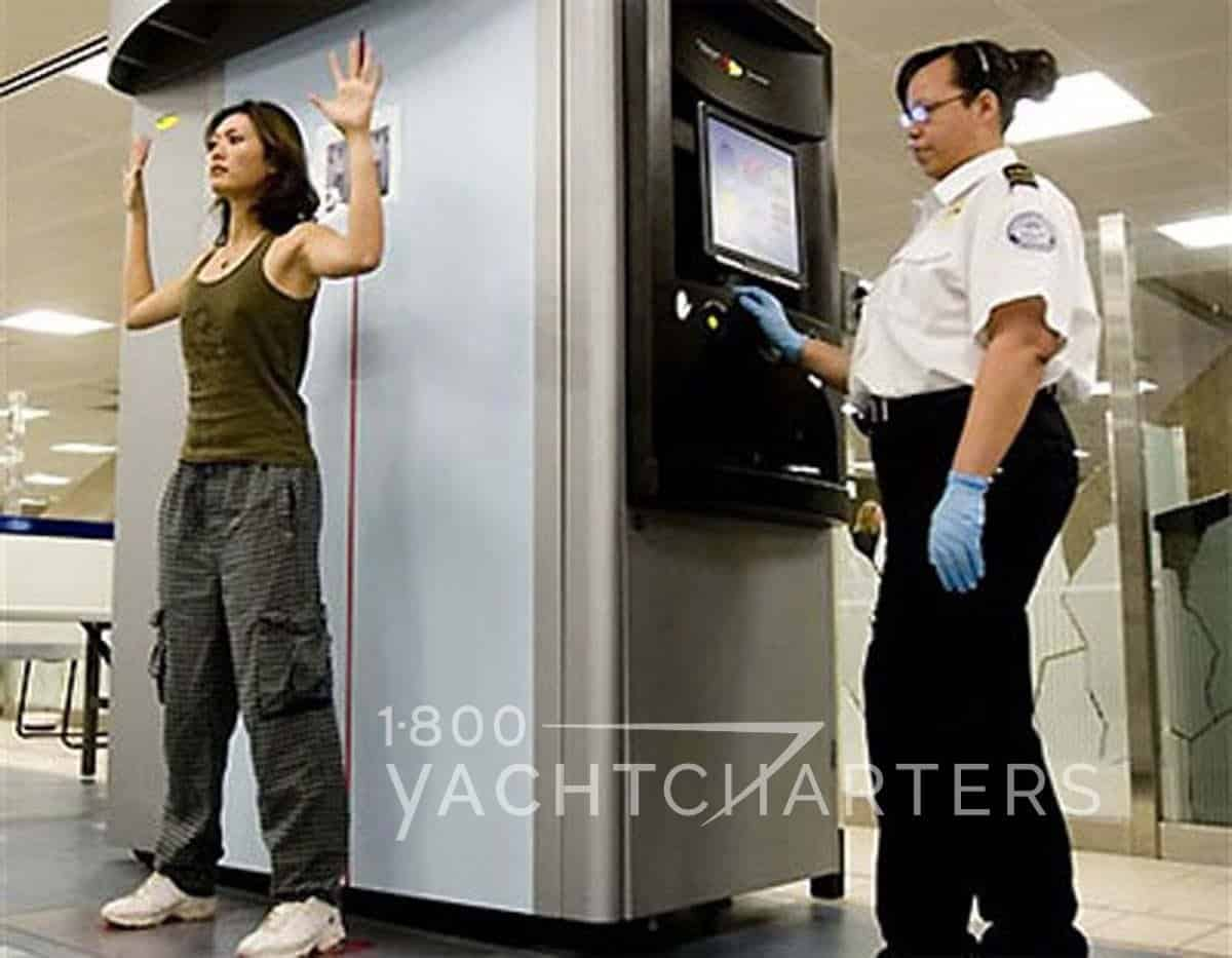 Photograph of a woman in an airport security body scanner. The passenger being scanned is at the left of the screen with her hands in the air while being scanned. The technician is standing on the right side of the photo, looking at a screen of the woman being scanned.